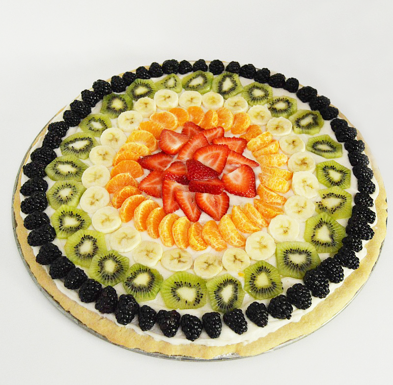 An easy and fun recipe for a fruit pizza with fresh cut fruit. This recipe uses a cheesecake cookie recipe and cream cheese buttercream frosting.